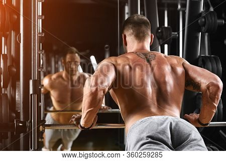 Fit And Muscular Man Doing Push-ups, Trains The Pectoral Muscles On The Block Simulator In The Gym.