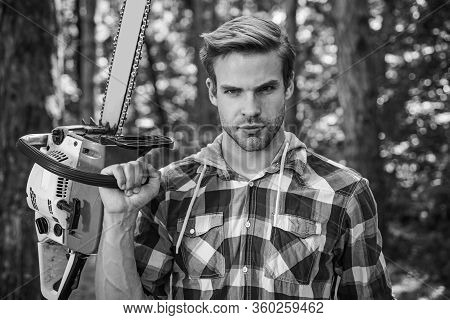 Lumberjack Worker Standing In The Forest With Chainsaw. Chainsaw. Stylish Young Man Posing Like Lumb