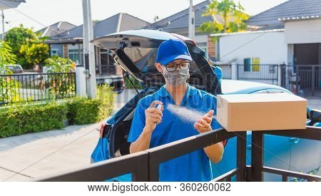 Asian Young Delivery Man Courier Online With Box In Uniform He Protective Face Mask And Squirt Spray