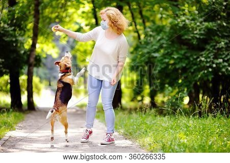 Young Beautiful Woman Wearing Disposable Medical Face Mask Playing With Beagle Dog In The Park Durin