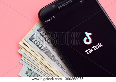 Tiktok Application On Samsung Smartphone Screen And Dollar Bills. Tiktok Is A Popular Video-sharing