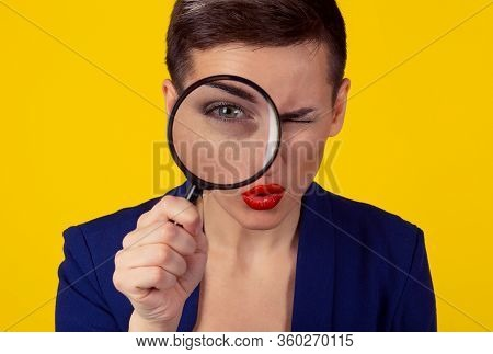 Skeptical Woman Looking Through Magnifying Glass Isolated Yellow Wall Background. Funny Woman Skepti