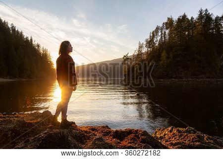 Adventurous Girl Hiking In The Canadian Landscape During A Vibrant Winter Sunset. Hike On Jug Island
