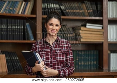 Happy university student holding books at the library. Portrait of young woman in college library looking at camera with copy space. Smiling proud girl in high school standing against book shelf.