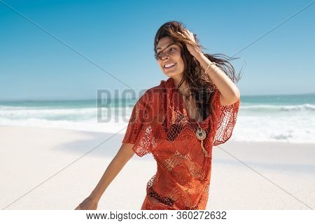 Beautiful latin woman running on tropical beach with copy space. Happy glamour and carefree woman walking on beach while looking behind. Stylish girl with black bikini enjoying summer vacation at sea.