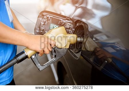 Close Up A Pump Hand Holding Refuel A Cars At Gasoline Station. Refueling Service. Gasoline Station.
