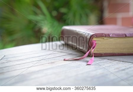 Holy Bible With Brown Color Cover On The Wood Table. Soft Blur With Focus On Fabric Book Mark.