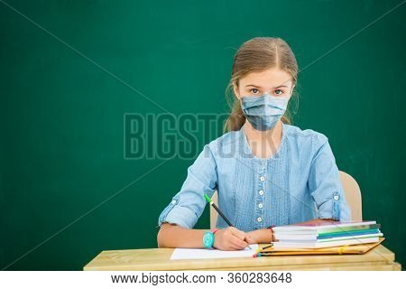 Back to school after quarantine girl sitting in the classroom against blackboard. Child in school with book and accessories. Education concept with copy space.