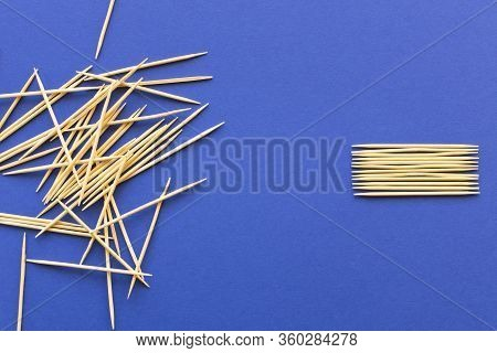 Lots Of Wooden Toothpicks On A Blue Background. The Concept Of Order And Chaos