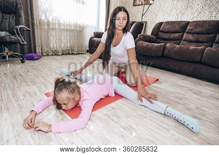 Family Mother And Child Daughter Are Engaged In Fitness, Yoga, Exercise At Home. Coach Puts Student