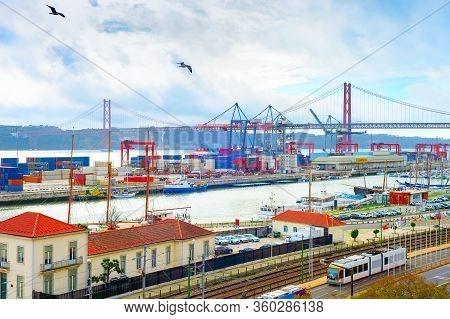 Seagulls Over Lisbon Commercial Port, Ships Containers And Freight Cranes, Skyline With 25th April B