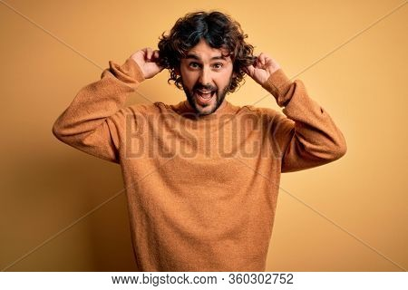 Young handsome man with beard wearing casual sweater standing over yellow background Smiling pulling ears with fingers, funny gesture. Audition problem