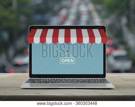 Modern Laptop Computer With Online Shopping Store Graphic And Open Sign On Wooden Table Over Blur Of