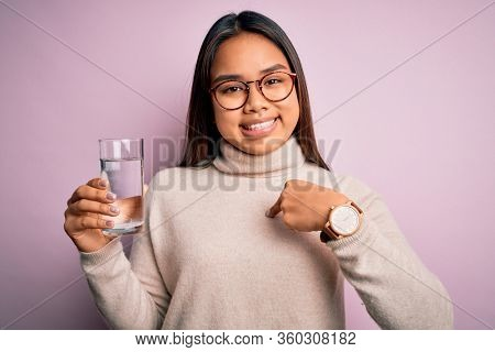 Young asian girl drinking glass of water to refreshment over isolated pink background with surprise face pointing finger to himself