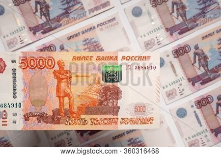 The Russian Bill Of 5000 Rubles Hangs Over A Field Of 500 Ruble Banknotes. View From Above. Close-up
