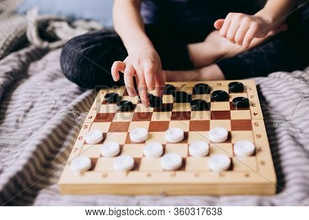 Young Kid Hands Playing Checkers Table Game On Bed. Stay At Home Quarantine Concept. Board Game And