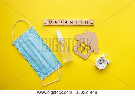 Top View Of A Yellow Background With The Word Quarantine. Protective Medical Mask, Alcohol Spray And