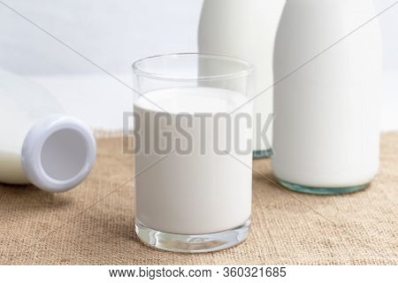 Bottle Of Milk And A Glass Of Milk On The Sackcloth With White Background For Food And Healthy Conce