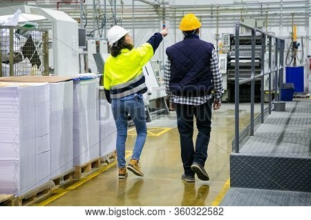 Back View Of Engineer And Inspector Pointing Fingers At Machines In Workshop. Man And Woman In Hardh