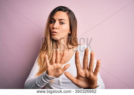 Young beautiful blonde woman with blue eyes wearing white t-shirt over pink background Moving away hands palms showing refusal and denial with afraid and disgusting expression. Stop and forbidden.