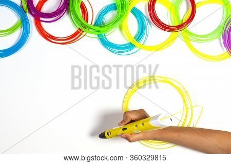 Kid Hand With 3d Pen And Colourful Plastic Filament On White Table Background. Top View
