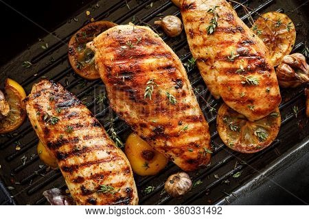 Grilled Chicken Breasts With Thyme, Garlic And Lemon Slices On A Grill Pan Close Up, Top View