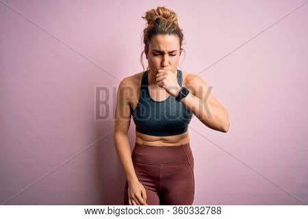 Young beautiful blonde sportswoman doing sport wearing sportswear over pink background feeling unwell and coughing as symptom for cold or bronchitis. Health care concept.