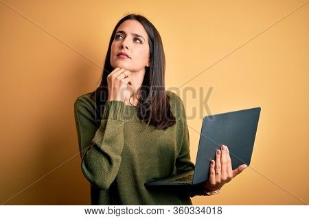 Young brunette woman with blue eyes working using computer laptop over yellow background with hand on chin thinking about question, pensive expression. Smiling with thoughtful face. Doubt concept.