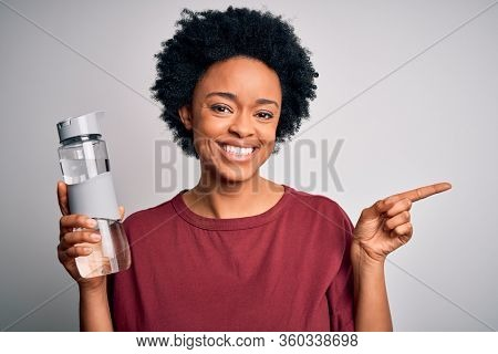 Young African American afro woman with curly hair drinking bottle of water for refreshment very happy pointing with hand and finger to the side