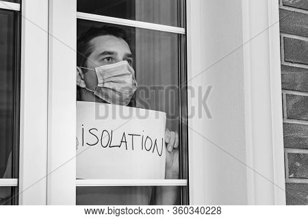 Man In A Medical Mask Holds A Tablet - Isolation. Isolation At Home For Self Quarantine. Home Quaran