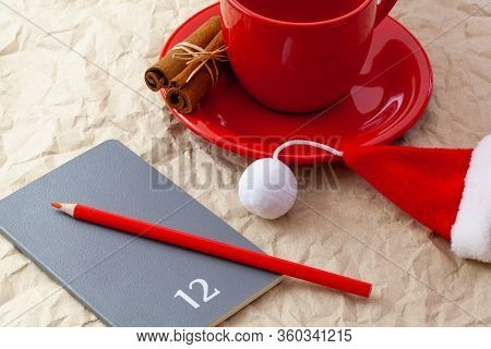 Photo Of Red Cup Of Coffee, Diary With Red Pencil. Plans For December. Near Diary Santa Claus Cap.