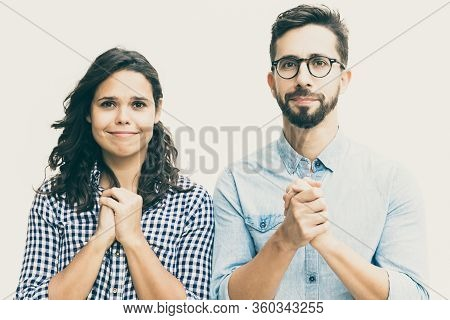 Excited Couple Hoping For Luck, Making Prayer Gesture. Young Woman In Casual And Man In Glasses Stan