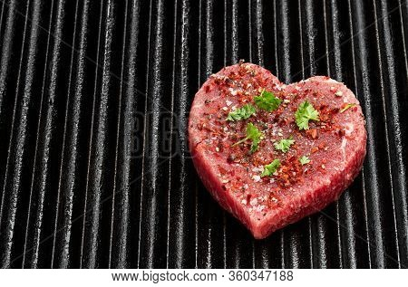 Heart  Shaped Raw Beef Meat With Spices On Grill Tray. Healthy Lifestyle Or Organic Food Concept For