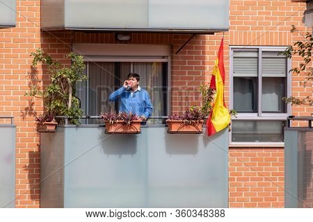 A man in balcony drinking after Spain imposed a lockdown to slow down the spread of the coronavirus disease in Valencia, Spain on April 5, 2020.