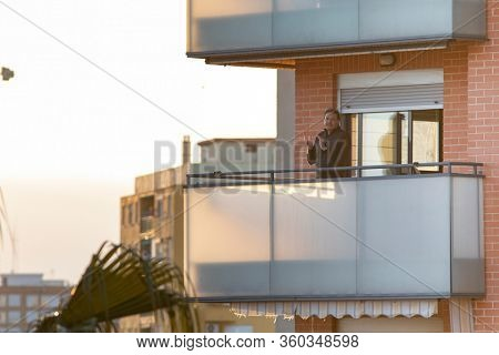 A man applaud at eight o'clock in balcony after Spain imposed a lockdown to slow down the spread of the coronavirus disease in Valencia, Spain on April 5, 2020.