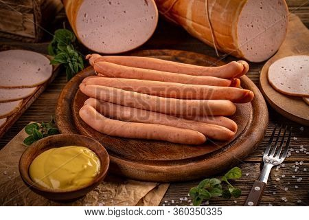 Raw Frankfurter Sausages With Mustard Sauce On Cutting Board Over Wooden Background