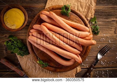 Frankfurter Sausage With Mustard On Rustic Wooden Cutting Board