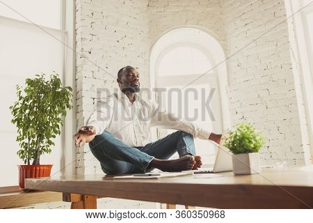 Young African-american Man Doing Yoga At Home While Being Quarantine And Freelance Online Working. R