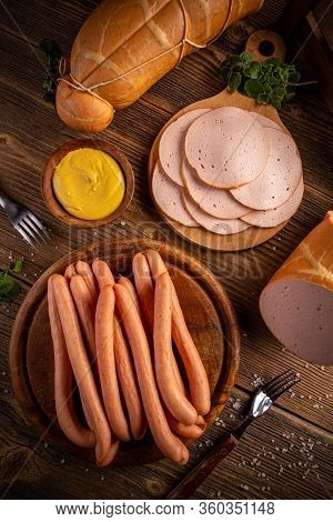 Poultry Cold Cuts And Hot Dog Sausages With Mustard On Wooden Background