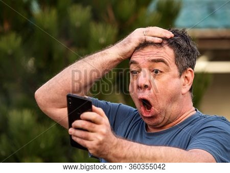 Shocked mature man with a smartphone in a park or forest