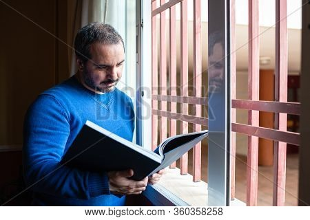 Man Reading A Book By The Window Dunring Quarantine