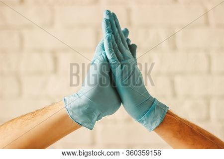 Two Men Clapping Hands In Protective Gloves. Doctors Wearing Medical Gloves On Hands Celebrating Suc