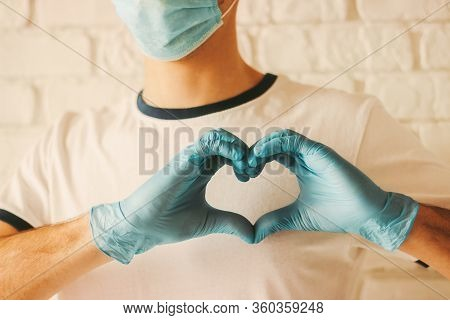 Young Doctor In Protective Gloves And Medical Mask On Face Showing Heart Symbol. Man In Medical Glov