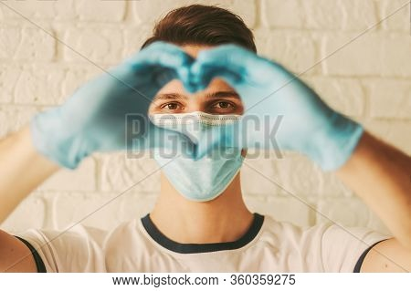 Young Man In Protective Latex Gloves And Medical Face Mask Gesturing Love Symbol By Hands. Doctor In