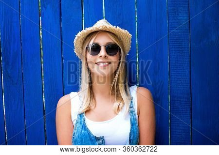 Pretty Teenage Hipster Girl With Toothy Smile In Straw Hat And Sunglasses Outdoor Over Blue Wooden B