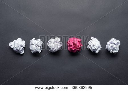 Crumpled Pink Paper Ball Among White Balls On Black Background. Extraordinary Solution Of Problem. B