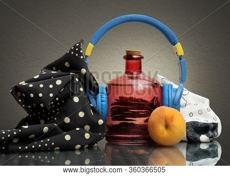 Still Life With Two Black And White Napkins, Blue Headphones, Vintage Glass Bottle And A Ripe Peach