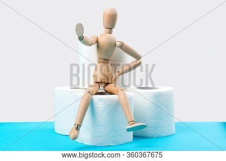 Stop Panic. Wooden Man Sitting On A Toilet Paper Rolls. Background With Stock Of Toilet Paper Rolls.