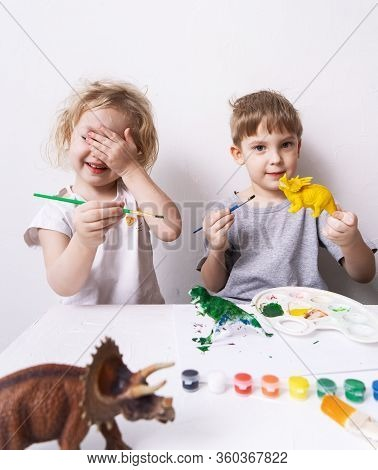 Children Boy And Girl Laugh Cheerfully Play And Paint With Toy And Brush Figures Of Toy Dinosaurs.