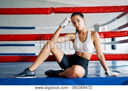 Young Beautiful Woman Relax Sitiing In Boxing Ring After Hard Workout. Sport Concept